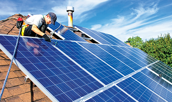 Photo of a man installing solar panels on a roof