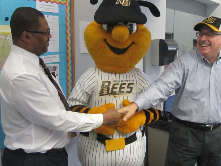 Photo of Alex Johnson shaking a man's hand and both men and standing with the New Britain Bees mascot