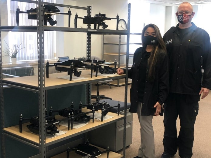 man and woman standing next a shelf full of drones